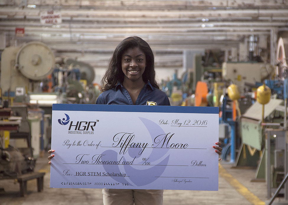 Tiffany Moore at HGR Industrial Surplus with $2,000 scholarship check