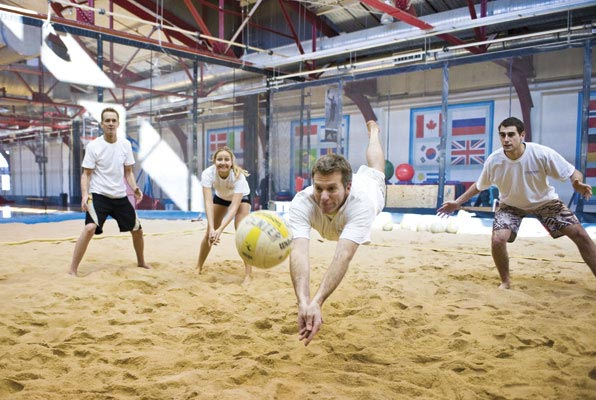 Men playing indoor sand volleyball