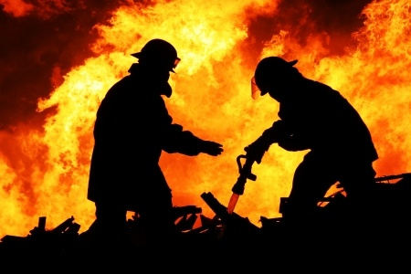 Silhouette of two firefighters fighting blazing fire and timber