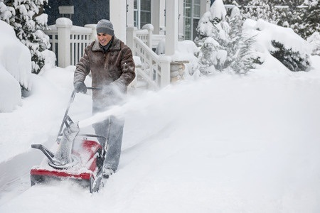 man using snowblower on sidewalk