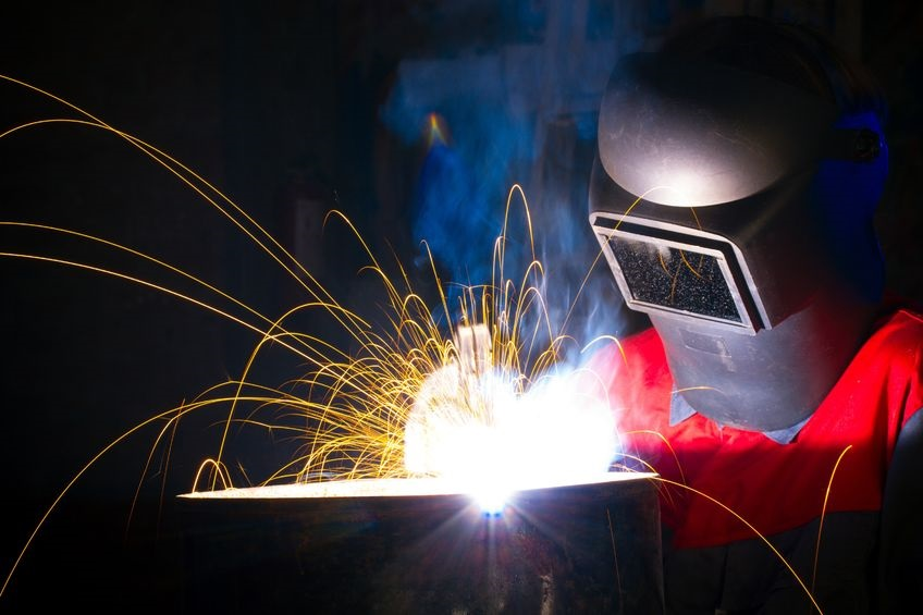welder with shield and sparks