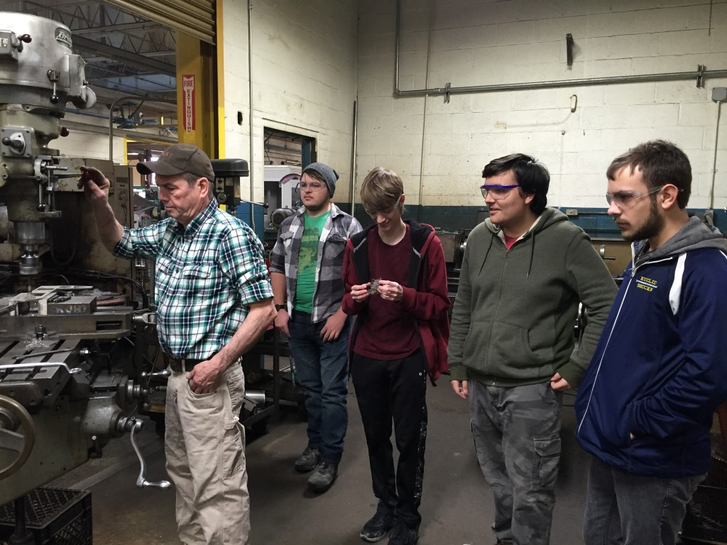 Euclid High School robotics students working at a drill press
