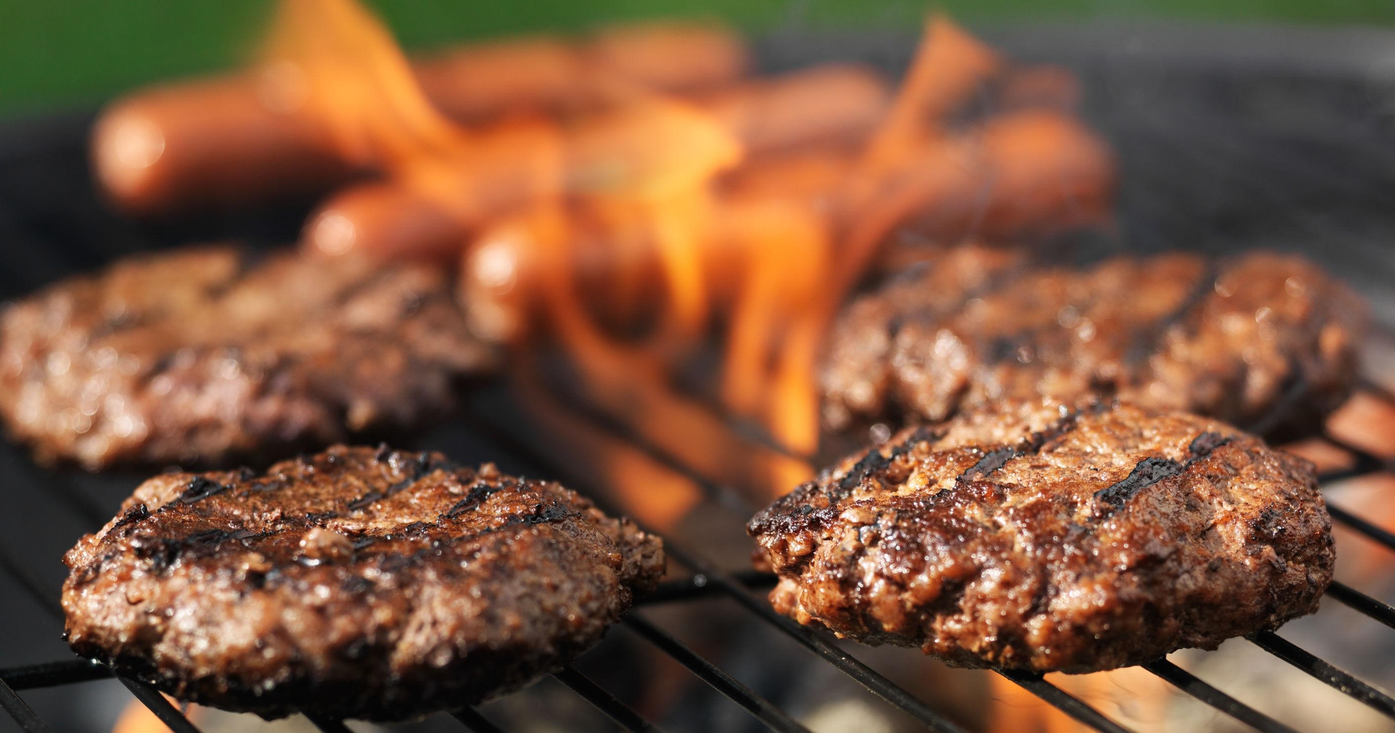madraí te agus hamburgers cookout ar an grill