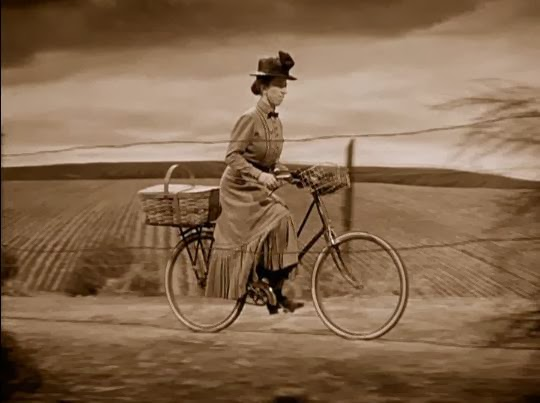 Miss Gulch from the Wizard of Oz riding a bicycle